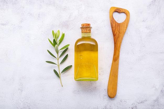 Glasflasche olivenöl und olivenzweig auf weißem betonhintergrund.