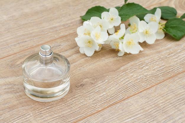 Glasflasche parfüm und zweig von jasminblüten auf den holzbrettern. konzept, an feiertagen ein geschenk zu machen. ansicht von oben.