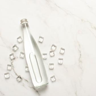 Glasflasche wasser- und eiswürfel auf einer marmortabelle.