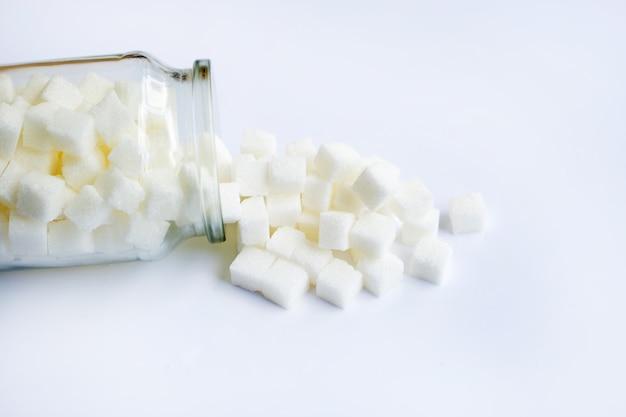 Glasflasche zuckerwürfel auf weiß