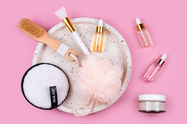 Glasflaschen der hautpflege-essenz, gesichtsschwamm, spa-bürste und waschlappen auf marmorkosmetiktablett auf rosa hintergrund