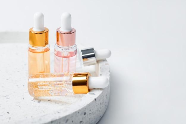 Glasflaschen der hautpflegeessenz auf marmorkosmetiktablett auf hellem hintergrund. vitamine für die haut