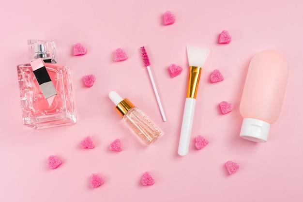 Glasflaschen der hautpflegeessenz, parfüm, körperlotion im plastikbehälter mit papiereinkaufstasche auf rosa hintergrund