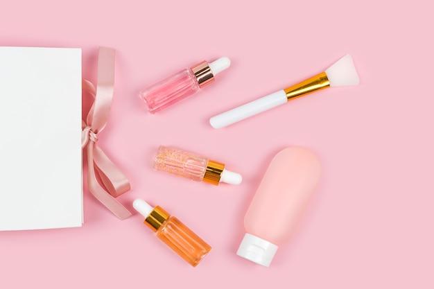Glasflaschen der hautpflegeessenz und körperlotion im plastikbehälter mit papiergeschenk-einkaufstasche auf rosa hintergrund