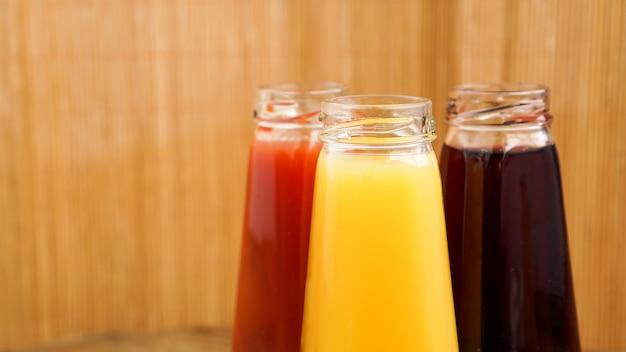 Glasflaschen frischer gesunder saft auf holzhintergrund. mehrfarbige säfte. sommerfoto und gesunder lebensstil, vitamine