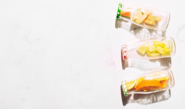 Glasflaschen mit farbigen kappen voll geschnittener zitrusfrucht