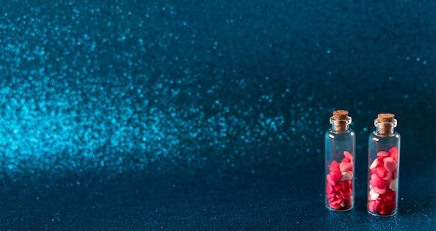 Glasflaschen mit herzförmigen zuckerstreuseln auf glitzerndem blauem hintergrund. valentinstag konzept, süße liebe.