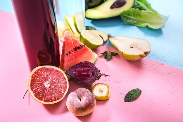 Glasflaschen mit natürlichen getränken an einer farbigen wand