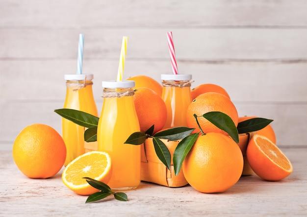 Glasflaschen organischer frischer orangensaft mit rohen orangen auf hellem hölzernem hintergrund