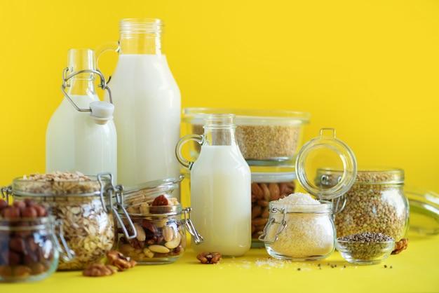 Glasflaschen pflanzenmilch und mandeln aus veganem gemüse, nüsse, kokosnuss, hanfsamenmilch auf gelbem hintergrund.