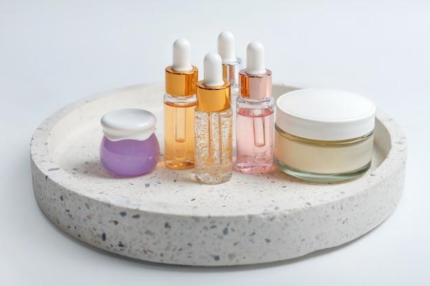 Glasflaschen und gläser der hautpflegeessenz mit gesichtscreme auf marmorkosmetiktablett auf hellem hintergrund