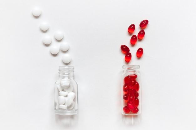Glasflaschen und skattered pillen auf weiß