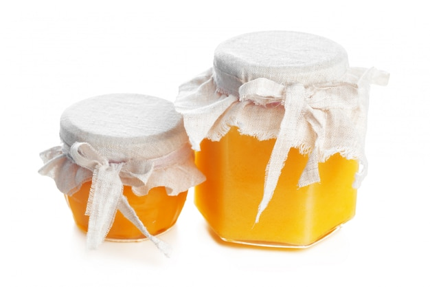 Glasgefäß mit dem süßen honig getrennt auf weiß