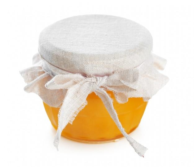 Glasgefäß mit dem süßen honig lokalisiert auf weißem hintergrund