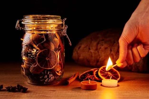 Glasgefäß mit kiefernkegeln und getrockneten orangen auf einem dunklen hintergrund. frau setzt festliche kerze in brand