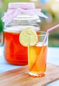 Glasgefäß mit kombucha, gegossenes glas mit kombucha und himbeeren im sommergarten horizontal.