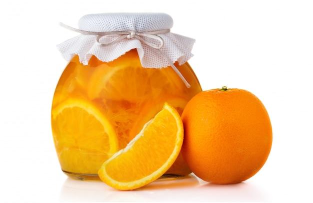 Glasgefäß mit orangenmarmelade schloss mit dem absacken des deckels, der auf weißem hintergrund lokalisiert wurde