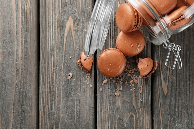 Glasgefäß und köstliche schokoladenmacarons auf holzoberfläche, ansicht von oben