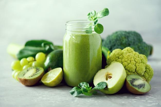 Glasgefäßbecher mit grünem gesundheit smoothie, kohlblätter, kalk, apfel, kiwi, trauben