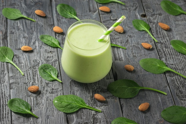 Glasglas mit avocado-getränk auf einem hintergrund von spinatblättern und mandeln. fitnessprodukt. diätetische sporternährung.