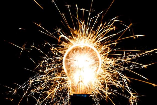 Glasglühbirne funkelt mit ideen, die aus dem kopf explodieren. konzept kreative arbeit mit abstraktem hintergrund, um zum denken anzuregen und neue goldene wege zu beschreiten