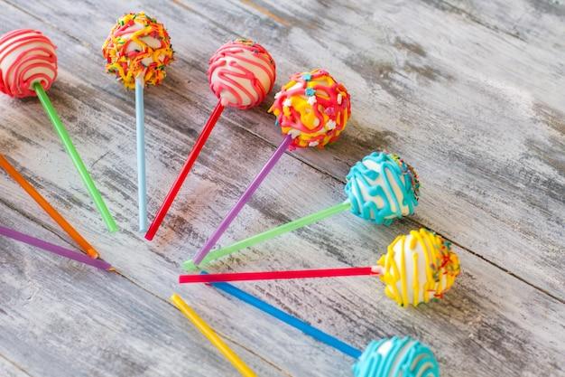 Glasierte bonbons auf stöcken. bunte bonbons auf hölzernem hintergrund. einfaches rezept für cake pops. kinder werden glücklich sein.