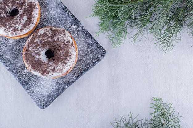 Glasierte donuts auf einer mit mehl bedeckten platte auf weißem hintergrund.