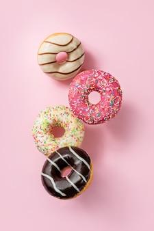Glasierte donuts, die auf einem rosa hintergrund schweben.