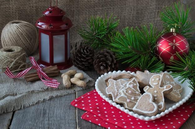 Glasierte hausgemachte kekse auf dem hintergrund von weihnachtsbaumzweigen und einer taschenlampe.