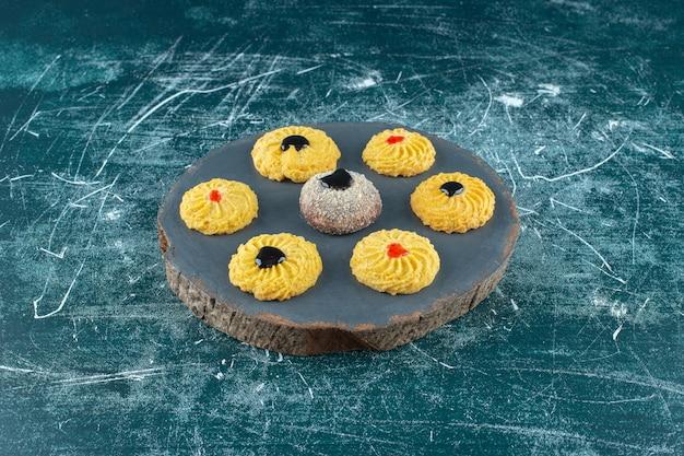 Glasierte kekse auf einem brett, auf blauem hintergrund. foto in hoher qualität