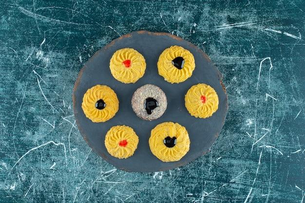 Glasierte kekse auf einem brett, auf dem blauen tisch.