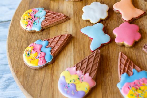 Glasierte kekse auf holzbrett. kekse in form von blumen. desserts für die hausparty. zuckerguss und knuspriger teig.