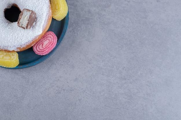 Glasierte onut mit schokoladenstückchen und umgeben von marmeladen auf marmoroberfläche