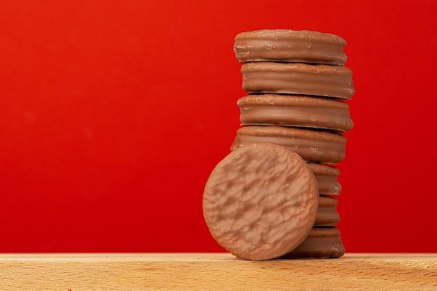 Glasierte schokoladenkekse stapeln auf vorderansicht des roten hintergrunds