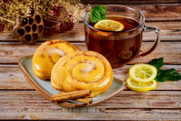 Glasierte zimtschnecken und eine tasse tee mit zitrone und minze