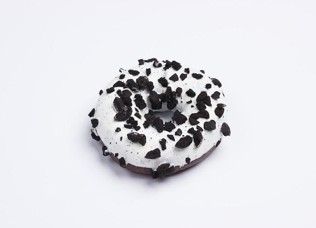 Glasierter donut mit schokoladenstücken auf weißem grund bestreut. süßigkeiten kuchen, ungesundes essen