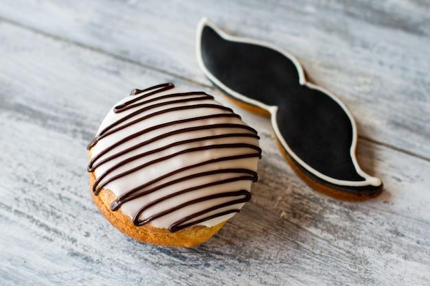 Glasierter keks in form eines schnurrbartes. kekse auf hölzernem hintergrund. leckeres gebäck aus dem laden. lecker und elegant.