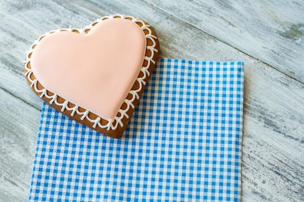 Glasierter keks in herzform. plätzchen auf karierter serviette. dessert für verliebte. finde wege, gefühle zu zeigen.