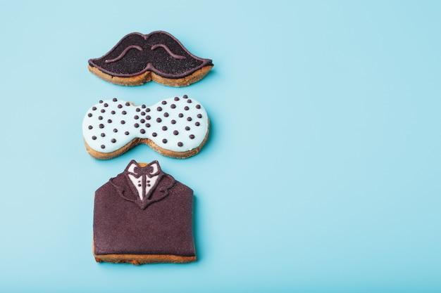 Glasierter lebkuchen in form von schnurrbart, schmetterling und smoking, herren-set. handgemachte kekse.