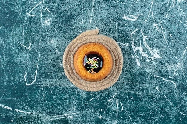 Glasierter minikuchen auf einem untersetzer, auf blauem hintergrund. foto in hoher qualität