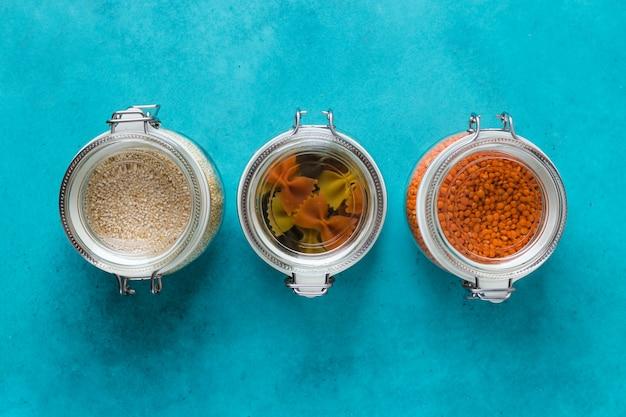 Glaskästen und flaschen mit quinoa, linsen, nudeln organisiert zu hause einfache stilvolle lagerung