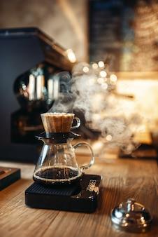 Glaskaffeekanne mit dampf auf hölzerner theke