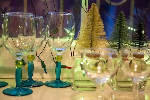 Glaskelche mit blauen beinen stehen auf einem weißen tisch am fenster neben kleinen dekorativen weihnachtsbäumen. nahaufnahme. gemütliches abendkonzept