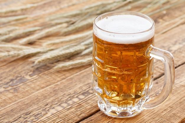 Glaskrug bier auf alten holzbrettern mit gerstenähren auf einem hintergrund.