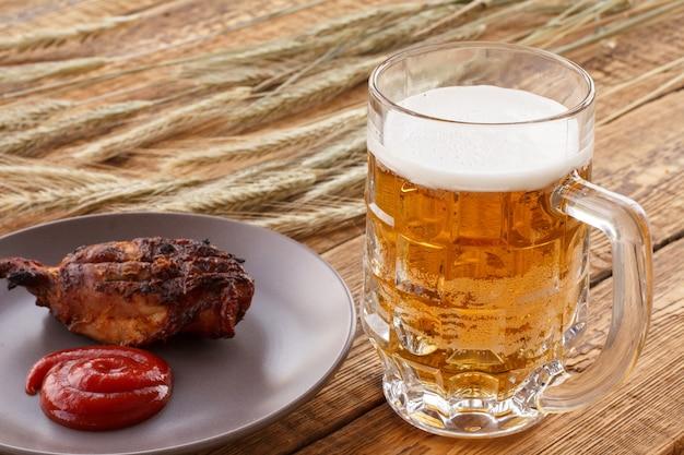 Glaskrug bier, teller mit gegrilltem hühnchen und tomatensauce, gerstenähren auf einem hintergrund. alles auf holzbrettern.