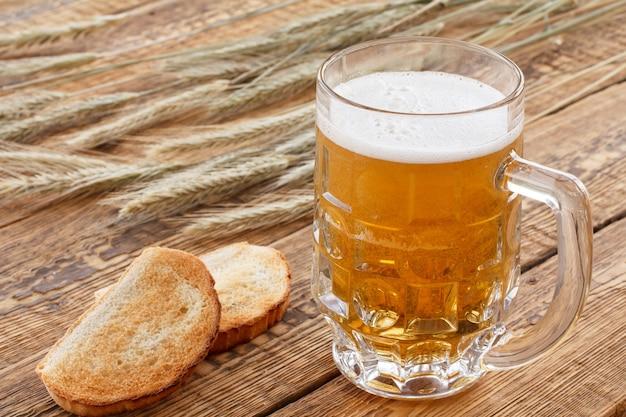 Glaskrug bier und brot auf holzbrettern mit gerstenähren auf einem hintergrund.