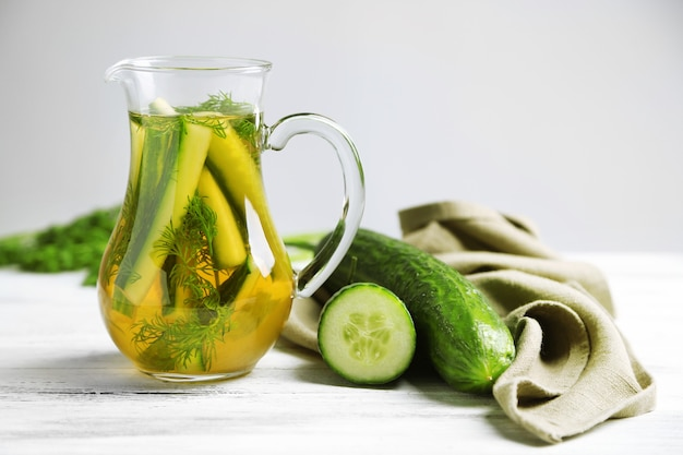 Glaskrug mit frischem bio-gurkenwasser auf holztisch
