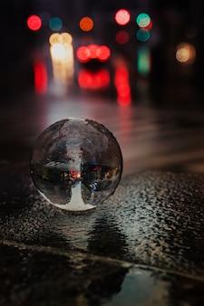 Glaskugel auf der straße unter dem regen mit einigen autolichtern