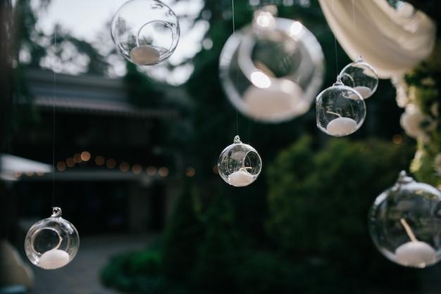 Glaskugeln mit kerzen hängen vom hochzeitsaltar