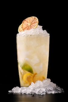 Glaslimonade mit limette und zitrone mit eis auf schwarzer tischnahaufnahme. kalte limonade oder cocktailkonzept